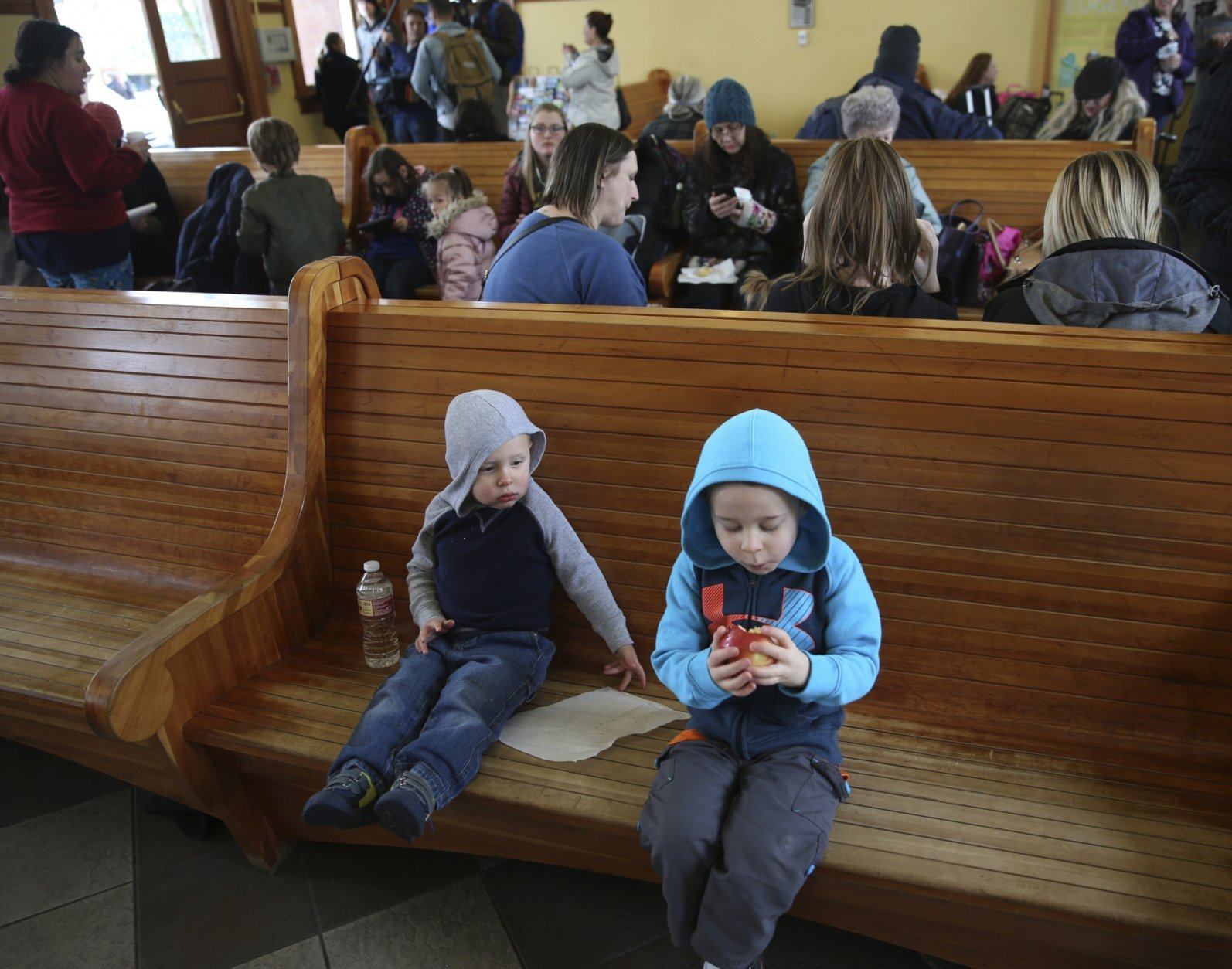 Ryder Albright, 2, left, and his brother Logan Albright, 5, get some food and water in the waiting area of the Eugene Amtrak Station with over a hundred other people after arriving, Tuesday, Feb. 26, 2019, Eugene, Ore., after being stranded with their parents overnight in the train in the mountains east of Eugene. (AP Photo/Chris Pietsch)