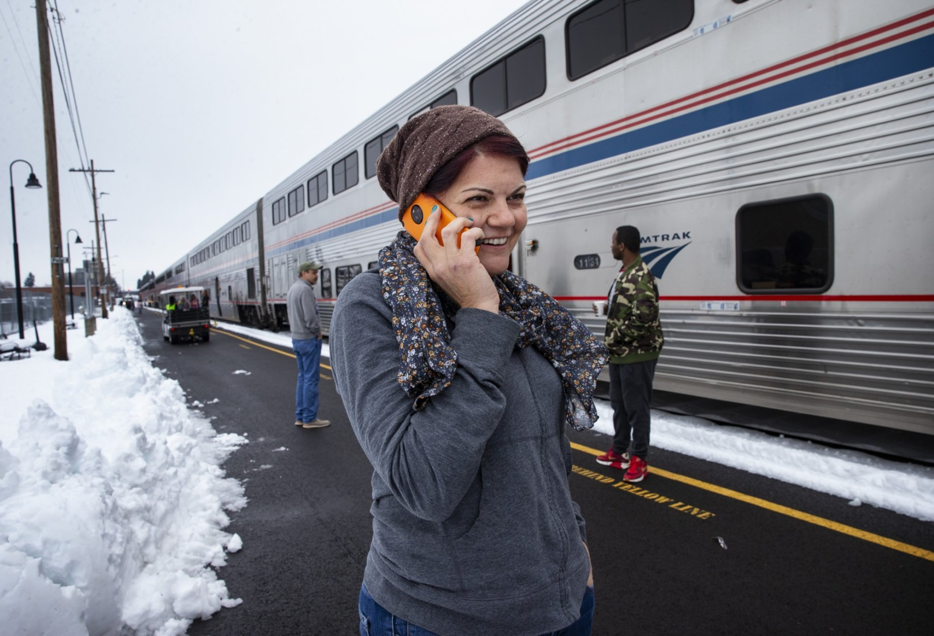 Tracy Rhodes, center, talks on the her phone while arriving in Eugene, Ore Tuesday, Feb. 26, 2019 after being stranded on the train overnight in the mountains east of Eugene, Ore. (AP Photo/Chris Pietsch)