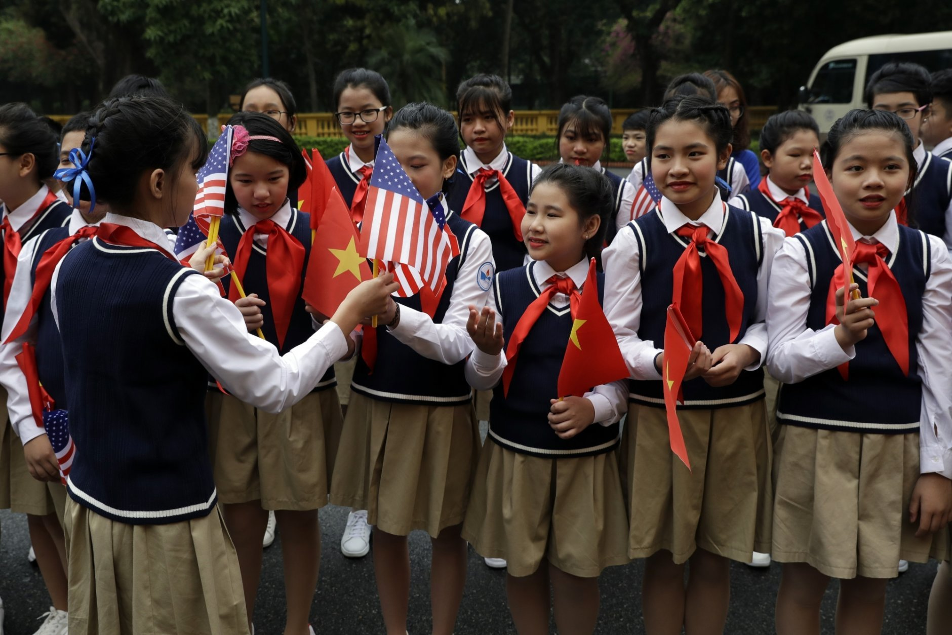 Children are handed American flags before U.S. President Donald Trump arrives to meet with Vietnamese President Nguyen Phu Trong at the Presidential Palace, Wednesday, Feb. 27, 2019, in Hanoi. (AP Photo/Evan Vucci)
