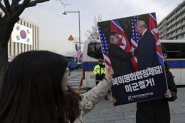 """A South Korean protester holds a banner showing a photo of U.S. President Donald Trump and North Korean leader Kim Jong Un during a rally near the U.S. embassy in Seoul, South Korea, Wednesday, Feb. 27, 2019. The second summit between U.S President Donald Trump and North Korean leader Kim Jong Un will take place in Hanoi on Feb. 27 and 28. The letters read """"Peace Agreement between U.S. and North Korea"""" and """"Withdrawal of U.S. troops."""" (AP Photo/Lee Jin-man)"""