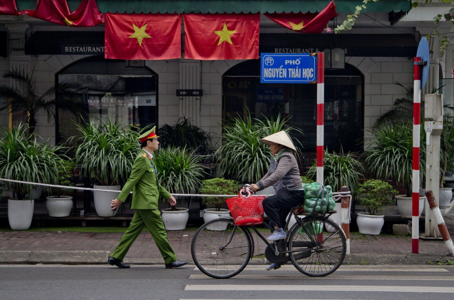 A woman rides a bicycle as a policeman walks past Vietnam flags in Hanoi, Vietnam, Wednesday, Feb. 27, 2019, as Vietnam prepare to facilitate the second summit between U.S President Donald Trump and North Korean leader Kim Jong Un in Hanoi. (AP Photo/Gemunu Amarasinghe)