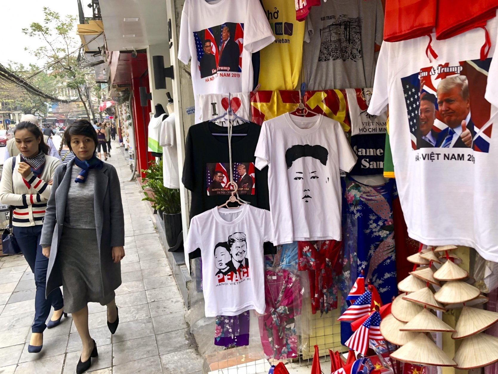 """A woman glances at a shop selling t-shirts marking the summit between U.S. President Donald Trump and North Korean leader Kim Jong Un in Hanoi, Vietnam, Wednesday, Feb. 27, 2019. Trump hoped for """"great things"""" from his second meeting with Kim as he paid a courtesy call on his Vietnamese hosts ahead of the summit in the Vietnamese capital. (AP Photo/Adam Schreck)"""