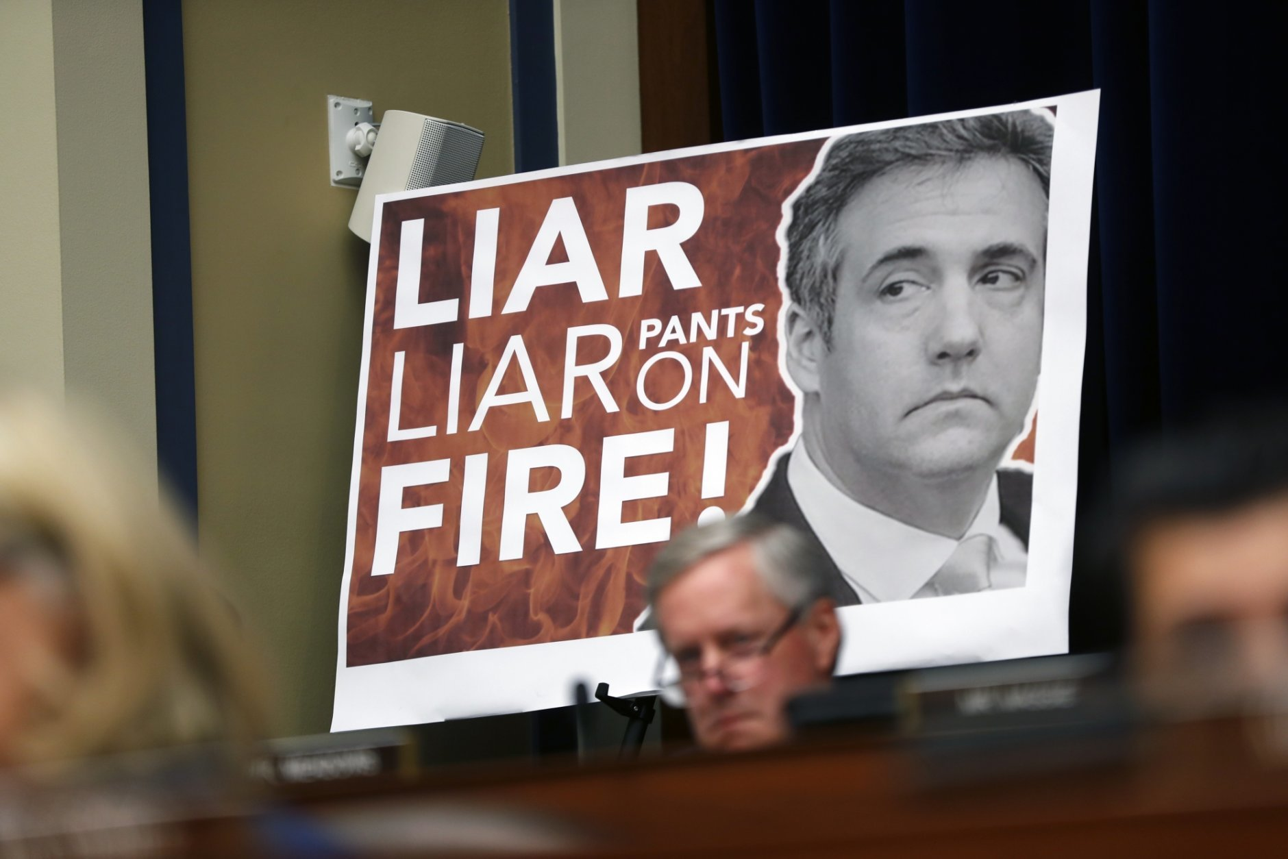 A poster on display during a hearing with Michael Cohen, President Donald Trump's former personal lawyer, before the House Oversight and Reform Committee on Capitol Hill in Washington, Wednesday, Feb. 27, 2019. (AP Photo/Pablo Martinez Monsivais)