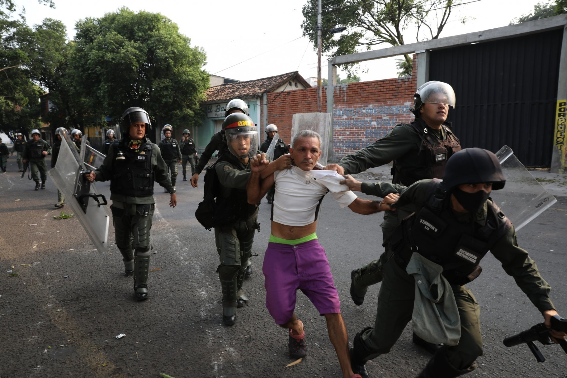 A man is detained during clashes with the Bolivarian National Guard in Urena, Venezuela, near the border with Colombia, Saturday, Feb. 23, 2019. Venezuela's National Guard fired tear gas on residents clearing a barricaded border bridge between Venezuela and Colombia on Saturday, heightening tensions over blocked humanitarian aid that opposition leader Juan Guaido has vowed to bring into the country over objections from President Nicolas Maduro. (AP Photo/Rodrigo Abd)