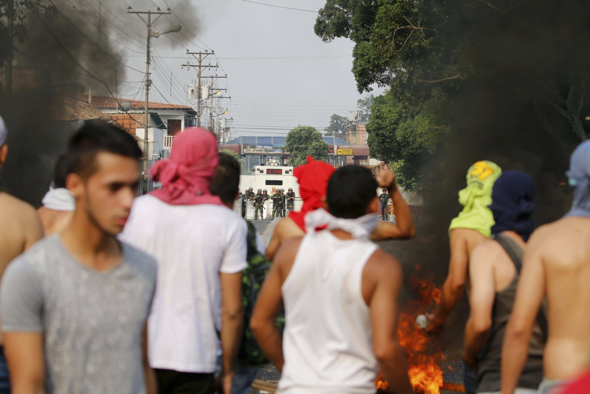 Opposition members pray during clashes with the Bolivarian National Guard in Urena, Venezuela, near the border with Colombia, Saturday, Feb. 23, 2019. Venezuela's National Guard fired tear gas on residents clearing a barricaded border bridge between Venezuela and Colombia on Saturday, heightening tensions over blocked humanitarian aid that opposition leader Juan Guaido has vowed to bring into the country over objections from President Nicolas Maduro(AP Photo/Fernando Llano)