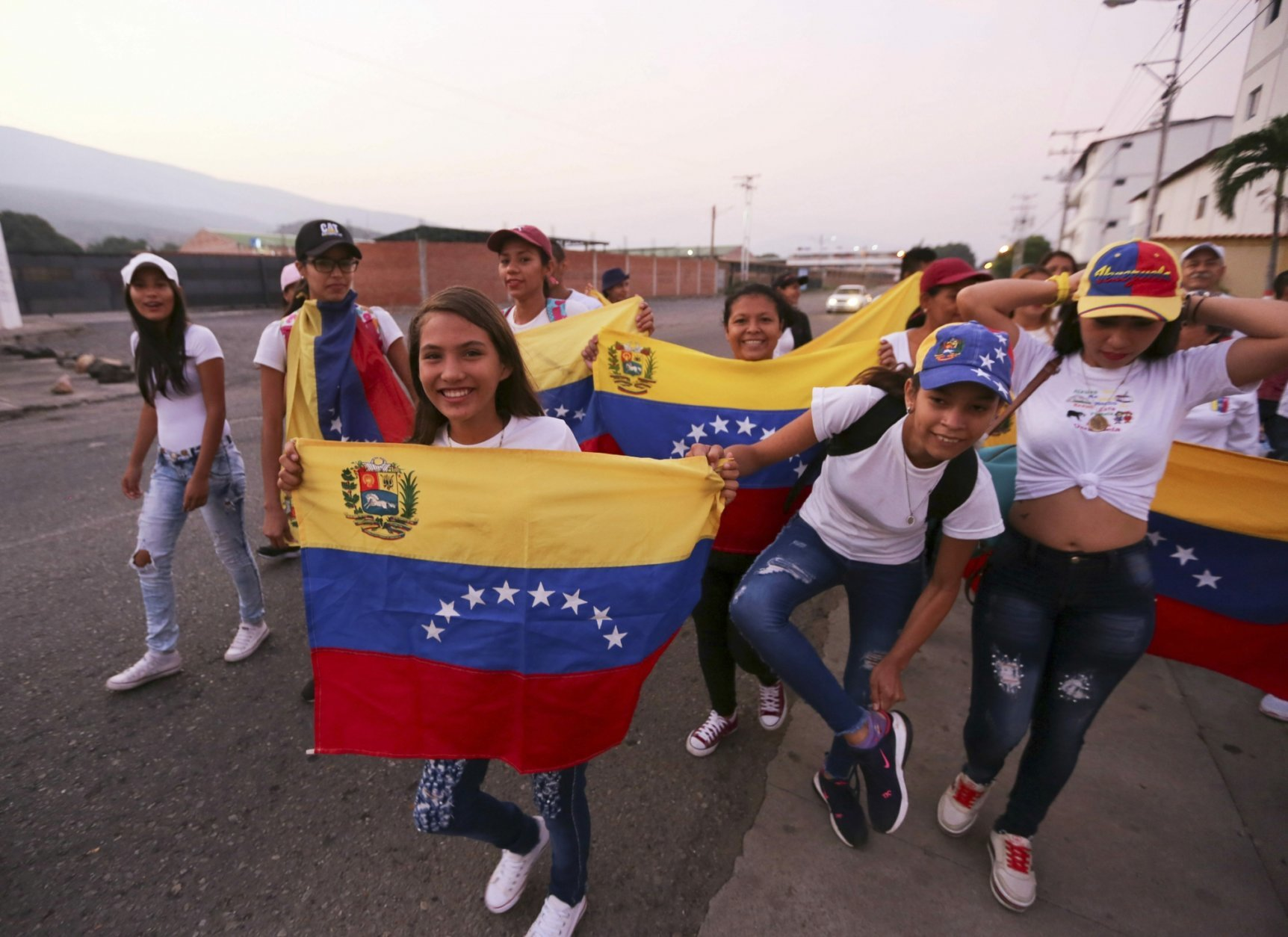 Youths wearing white T-shirts and Venezuelan flags prepare to cross through an unmarked trail to sneak into Colombia for the Venezuela Aid Live concert, in Palotal, Venezuela, Friday, Feb. 22, 2019. Venezuela's power struggle is set to become a battle of the bands Friday when musicians demanding President Nicolas Maduro allow in humanitarian aid and those supporting his refusal sing in rival concerts being held at both sides of a border bridge where tons of donated food and medicine are stored.(AP Photo/Fernando Llano)