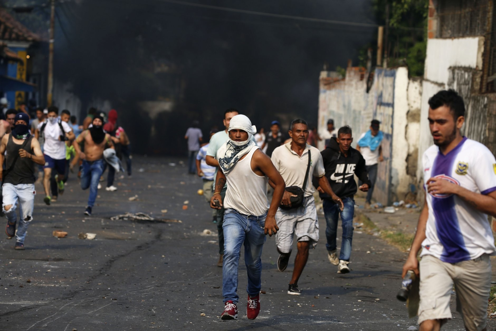 Demonstrators run during clashes with the Bolivarian National Guard in Urena, Venezuela, near the border with Colombia, Saturday, Feb. 23, 2019. Venezuela's National Guard fired tear gas on residents clearing a barricaded border bridge between Venezuela and Colombia on Saturday, heightening tensions over blocked humanitarian aid that opposition leader Juan Guaido has vowed to bring into the country over objections from President Nicolas Maduro. (AP Photo/Fernando Llano)