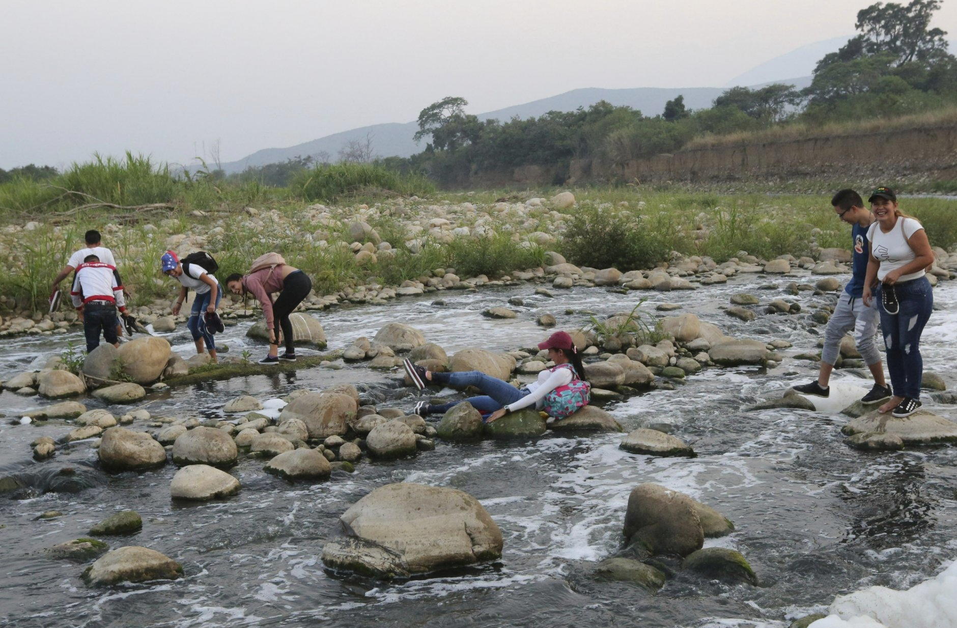 A young woman slips as she tries to cross the Tachira river into Colombia to attend the Venezuela Aid Live concert, in Palotal, Venezuela, Friday, Feb. 22, 2019. Venezuela's power struggle is set to become a battle of the bands Friday when musicians demanding President Nicolas Maduro allow in humanitarian aid and those supporting his refusal sing in rival concerts being held at both sides of a border bridge where tons of donated food and medicine are stored.(AP Photo/Fernando Llano)