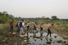 Youths walk across the Tachira river into Colombia for the Venezuela Aid Live concert, in Palotal, Venezuela, Friday, Feb. 22, 2019. Venezuela's power struggle is set to become a battle of the bands Friday when musicians demanding President Nicolas Maduro allow in humanitarian aid and those supporting his refusal sing in rival concerts being held at both sides of a border bridge where tons of donated food and medicine are stored.(AP Photo/Fernando Llano)
