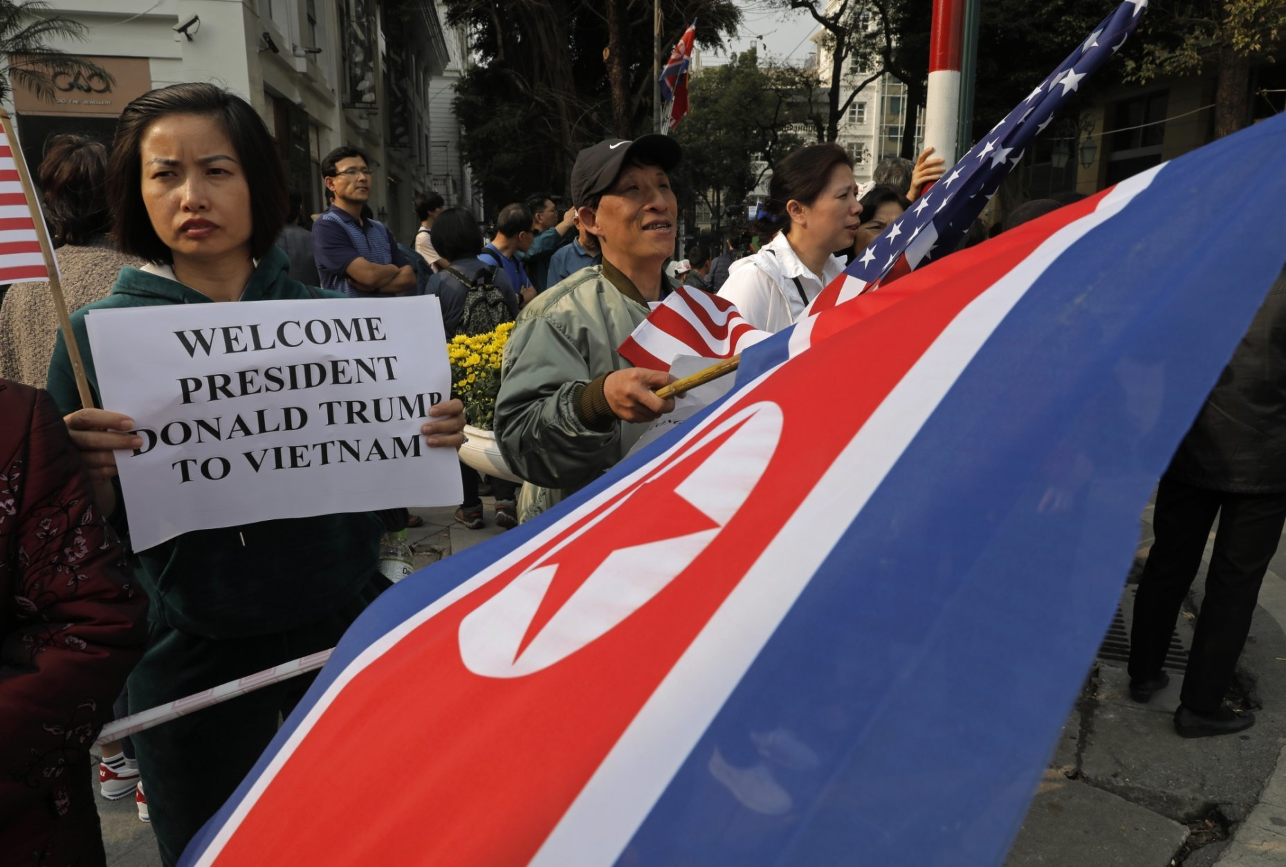 People hold placards and U.S. and North Korea flags outside the Metropole hotel where U.S. President Donald Trump and North Korean leader Kim Jong Un will have dinner in Hanoi, Vietnam, Wednesday, Feb. 27, 2019. The second summit between Trump and North Korean leader Kim Jong Un will take place in Hanoi on Feb. 27 and 28. (AP Photo/Vincent Yu)