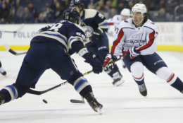 Washington Capitals' T.J. Oshie, right, carries the puck across the blue line as Columbus Blue Jackets' David Savard defends during the third period of an NHL hockey game Tuesday, Feb. 12, 2019, in Columbus, Ohio. The Blue Jackets beat the Capitals 3-0. (AP Photo/Jay LaPrete)