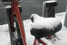 A cold, and wet ride: Snow gathers on a Capital Bikeshare seat in Friendship Heights on Wednesday morning. (WTOP/Sarah Beth Hensley)