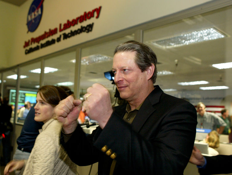 Former Vice-President Al Gore congratulates members of the Mars Exploration Rover team in the Mission Control Center at NASA's JPL in Pasadena, Calif., Saturday Jan. 24, 2004. following the safe landing of the Opportunity rover. (AP Photo/Damian Dovarganes/Pool)
