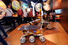 Visitors look at a Mars Rover exhibit in the new visitor's center at NASA's Jet Propulsion Laboratory during its annual two-day open house, Sunday, May 16, 2010, in Pasadena, Calif. in the forground is a replical of Pathfinder and in the background is replica of Spirit and Opportunity. (AP Photo/Mark J. Terrill)