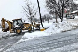 A backhoe begins the messy task of cleaning up the snow in Purcellville. (WTOP/Neal Augenstein)
