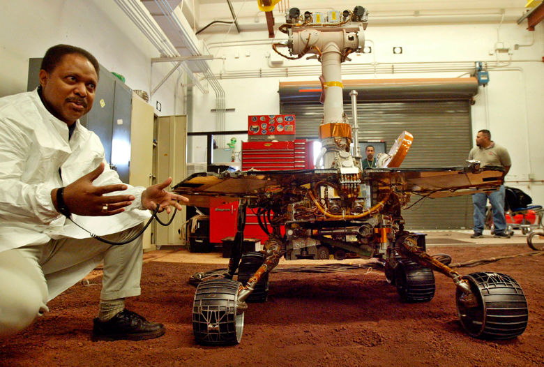 Edward Tunstel Jr., left, a mobility engineer, briefs a reporter about the capability of the Mars rovers Spirit and Opportunity using this full-scale working version, at NASA's Jet Propulsion Laboratory, in Pasadena, Calif. Mars has a nasty habit of living up to its mythological name and besting Earth when it comes to accepting visitors. NASA's InSight is the latest spacecraft to come calling, with every intent of landing and digging deeper into the planet than anything that's come before. The lander arrives at Mars on Monday, Nov. 26 following a six-month journey. (AP Photo/Ric Francis, File)