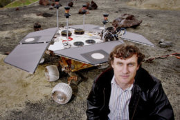Steve Squyres, principal scientist of NASA's Mars Exploration Rover program, poses next to a full scale copy, minus some instruments, of Spirit and Opportunity, two identical robot explorers currently enroute to Mars, at a mockup of the Martian surface in a parking lot behind the Jet Propulsion Laboratory in Pasadena, Calif., Nov. 21, 2003. The NASA rover program is just one of several missions that in the next few weeks will try to provide answers to questions scientists have aboutthe Red Planet. (AP Photo/Reed Saxon)