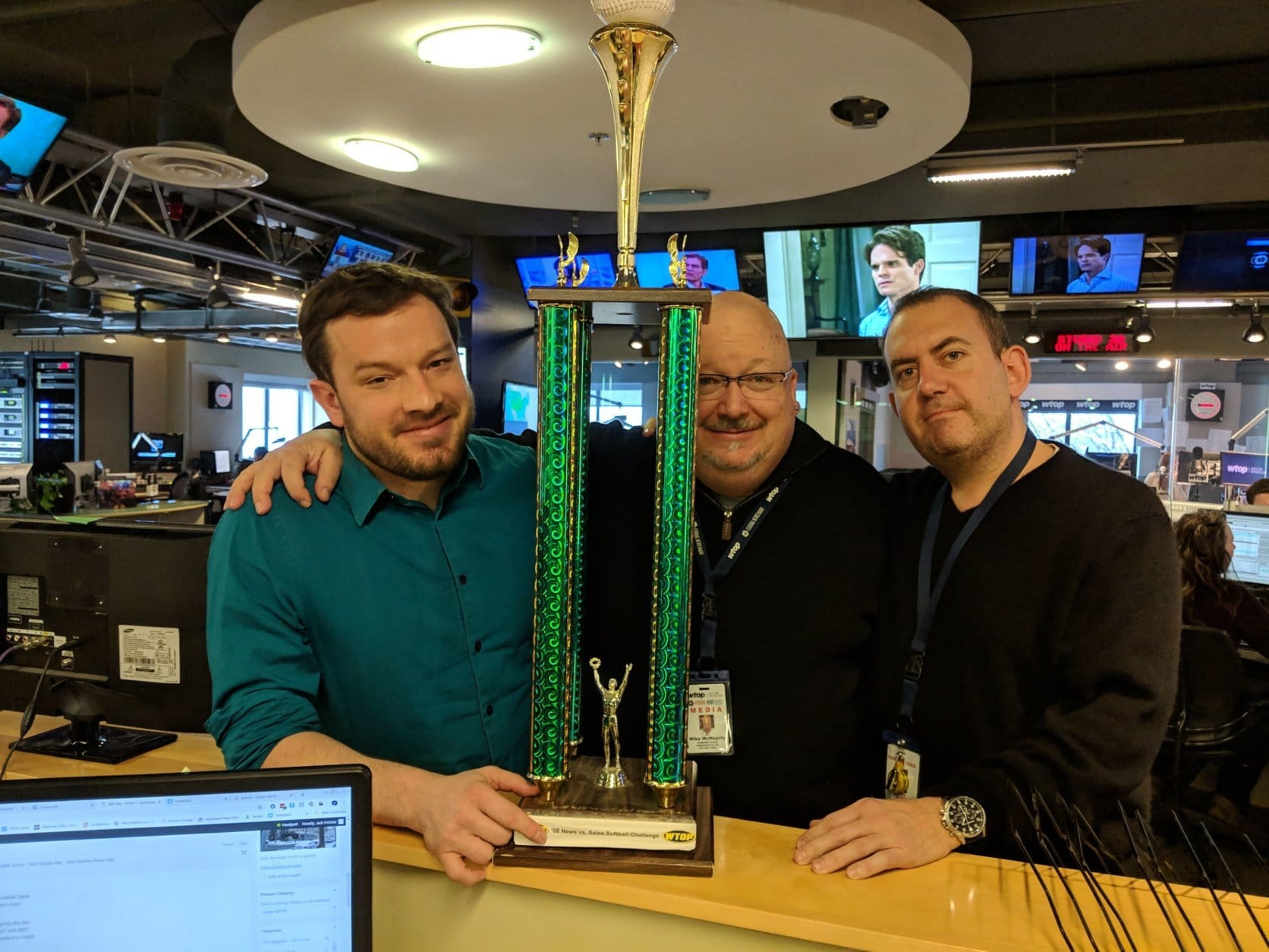 From left: Jason Fraley, news director Mike McMearty and sports anchor George Wallace share one last moment with the 2008 news-vs.-sales softball trophy. News won it so many times that it's a sore subject in the sales department. (WTOP/Jack Pointer)