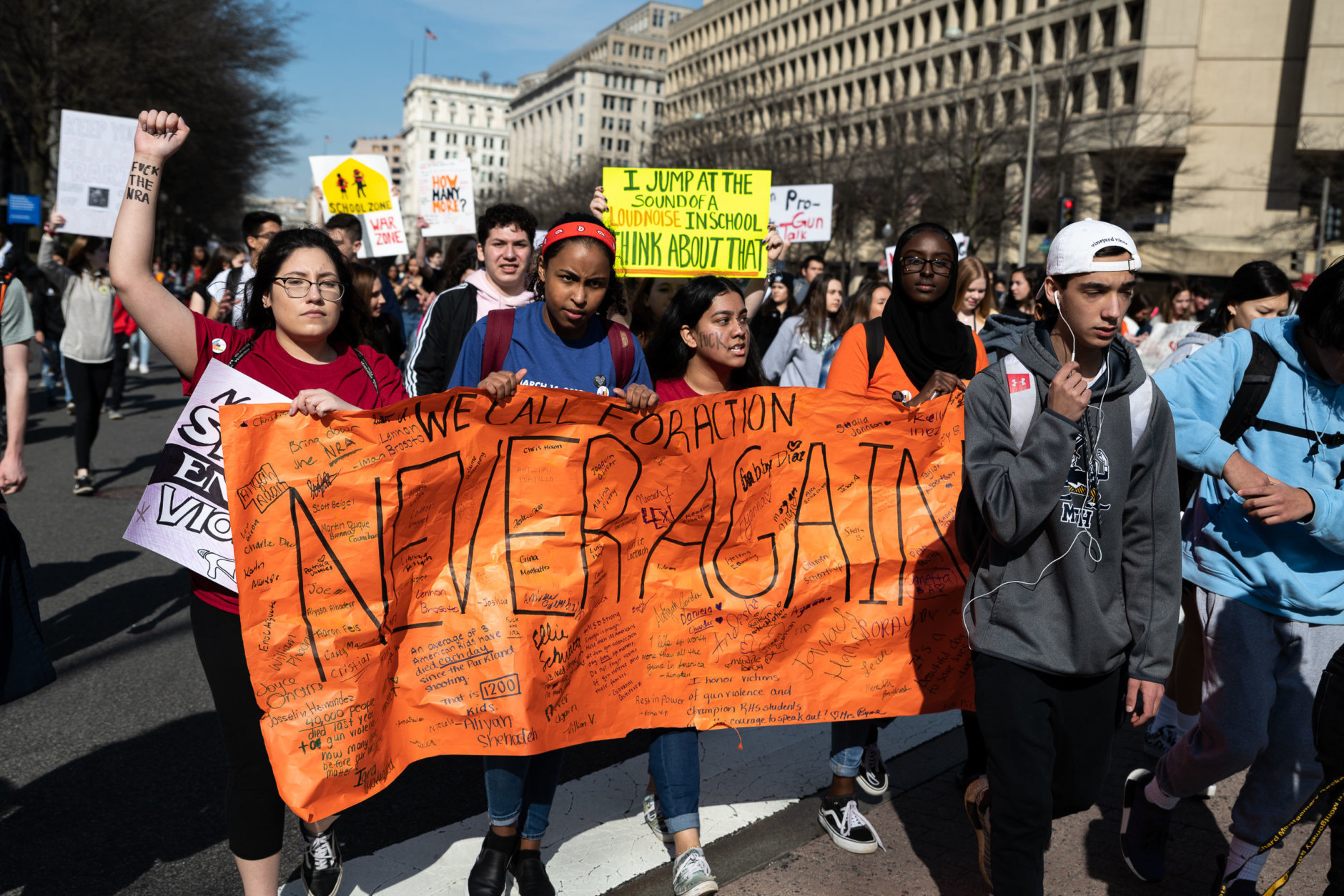 A banner signed by actiivsts is carried down Pennsylvania Avenue during a 2-mile gun control march to the Capitol led by Montgomery County-based student group, MoCo Students for Change. (WTOP/Alejandro Alvarez)