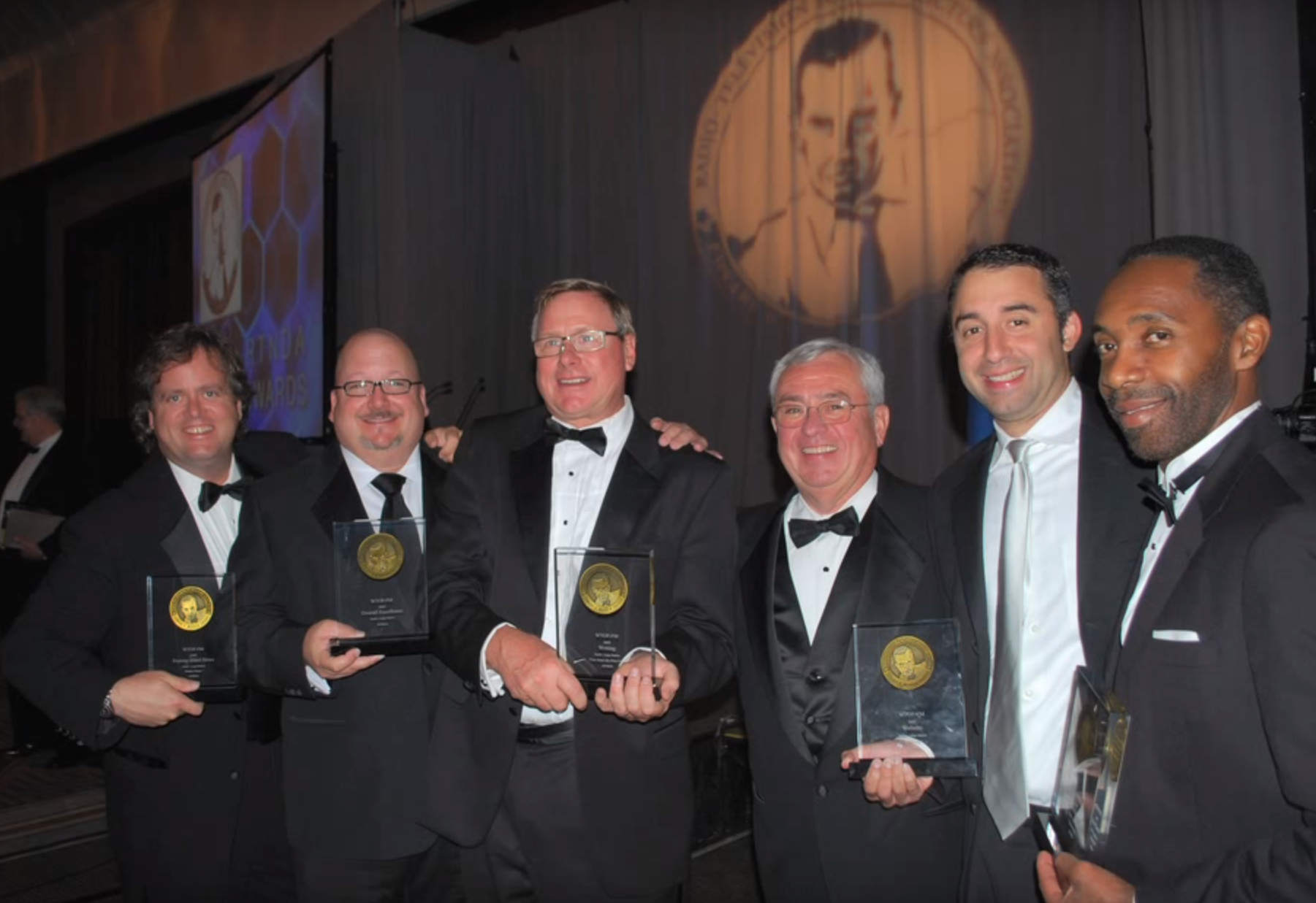 WTOP celebrated six national Murrow Award victories in ___. From left: Brennan Haselton, current Director of News/Programming Mike McMearty, commentator Chris Core, then-director of news/programming Jim Farley, ______ and national security correspondent J.J. Green. (File photo)