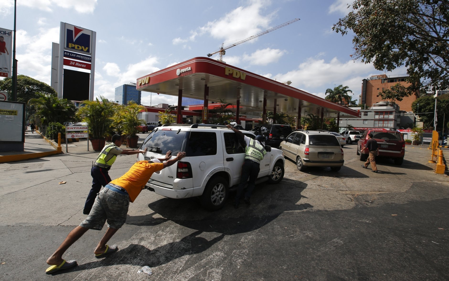 People push a car without fuel to one of the few gas stations that has its own electric generator during an electricity blackout in Caracas, Venezuela, Sunday, March 10, 2019. Power and communications outages continue to hit Venezuela, intensifying the hardship of a country paralyzed by economic and political crisis and heightening tension between the bitterly divided factions which accuse each other of being responsible for the collapse of the power grid. (AP Photo/Eduardo Verdugo)