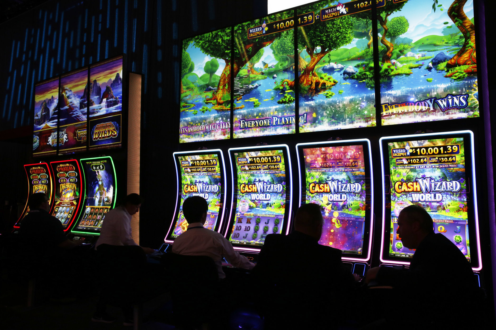People sit at electronic slot machines at the Scientific Games booth during the Global Gaming Expo, Wednesday, Oct. 10, 2018, in Las Vegas. (AP Photo/John Locher)