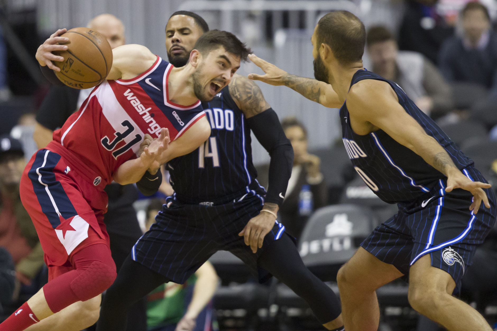 Washington Wizards guard Tomas Satoransky, left, from the Czech Republic, drives against Orlando Magic guards D.J. Augustin and Evan Fournier, right, from France, during the first half of an NBA basketball game Wednesday, March 13, 2019, in Washington. (AP Photo/Alex Brandon)
