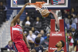 Washington Wizards center Thomas Bryant (13) dunks in front of Orlando Magic guard Terrence Ross, left, and center Khem Birch during the first half of an NBA basketball game Wednesday, March 13, 2019, in Washington. (AP Photo/Alex Brandon)