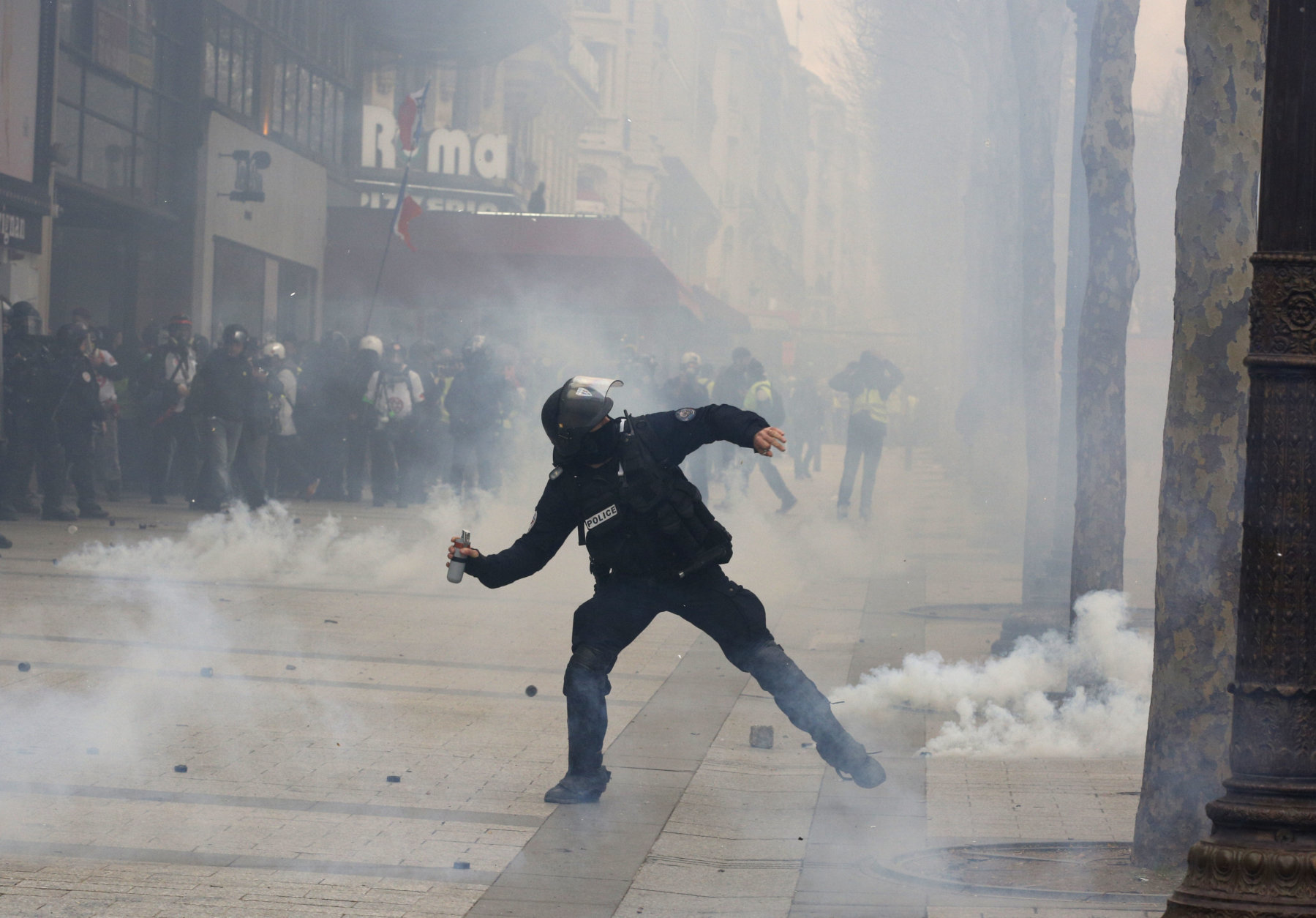 A riot police officer throws a tera gas canister onto protesters during a yellow vests demonstration on the Champs Elysees avenue Saturday, March 16, 2019 in Paris. French yellow vest protesters clashed Saturday with riot police near the Arc de Triomphe as they kicked off their 18th straight weekend of demonstrations against President Emmanuel Macron. (AP Photo/Christophe Ena)