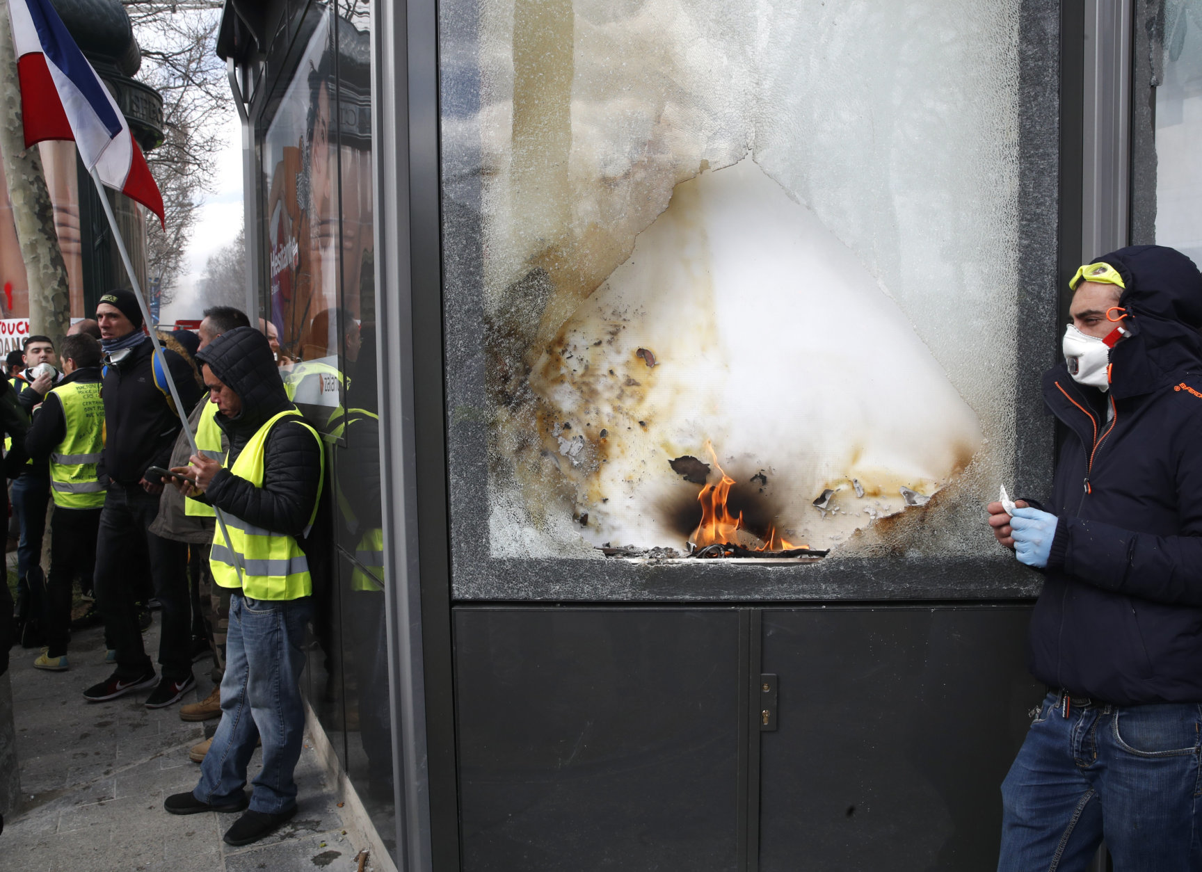 Yellow vests protesters stand by a damages shop during a demonstration, Saturday, March 16, 2019 in Paris. French yellow vest protesters clashed Saturday with riot police near the Arc de Triomphe as they kicked off their 18th straight weekend of demonstrations against President Emmanuel Macron. (AP Photo/Christophe Ena)