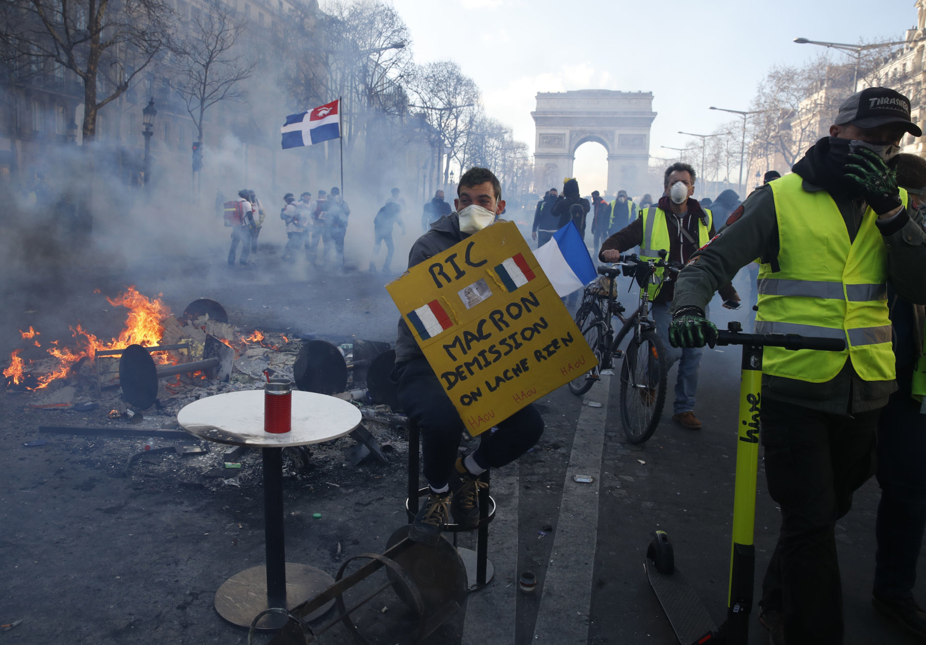 Yellow vests demonstrators walks down the Champs Elysees avenue Saturday, March 16, 2019 in Paris. Paris police say more than 100 people have been arrested amid rioting in the French capital by yellow vest protesters and clashes with police. They set life-threatening fires, smashed up luxury stores and clashed with police firing tear gas and water cannon. Poster reads: Macron resigns. (AP Photo/Christophe Ena)