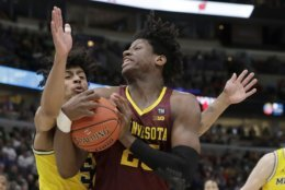 Minnesota's Daniel Oturu (25) grabs a rebound against Michigan's Eli Brooks during the first half of an NCAA college basketball game in the semifinals of the Big Ten Conference tournament, Saturday, March 16, 2019, in Chicago. (AP Photo/Nam Y. Huh)