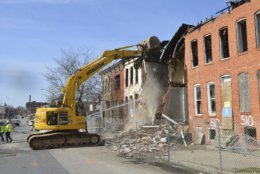 "Work crews demolish a derelict block as Baltimore tries to reduce its sea of boarded-up properties, Wednesday, March 13, 2019.   Mayor Catherine Pugh says her administration is committed to eliminating abandoned houses to ""pave the way for new investment and long-awaited revitalization."" She got in an excavator Wednesday to start the demolition in a blighted swath of West Baltimore. (AP Photo/David McFadden)"