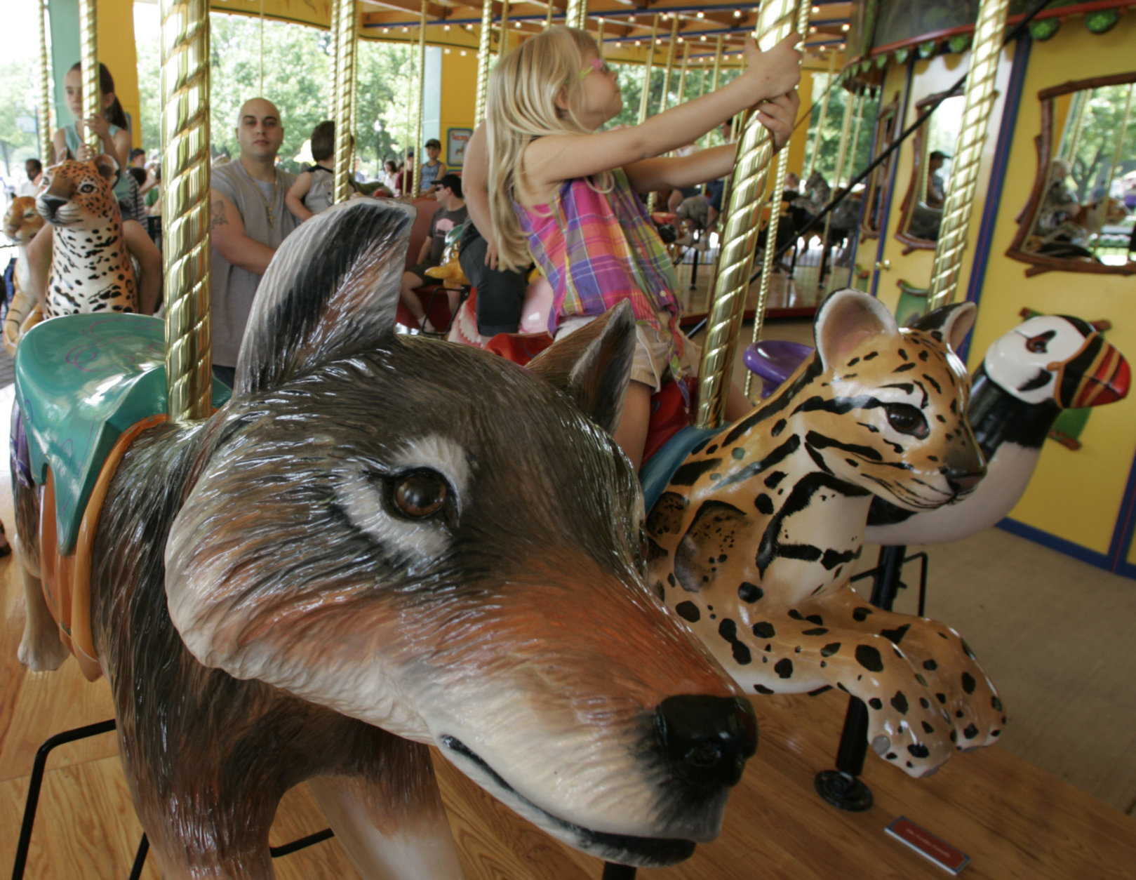 Paige McCoy rides a leopard cub on Brookfield Zoo's new carousel Saturday May, 27, 2006 in Brookfield, Ill. The new attraction is the largest non-restored hand carved wooden carousel in the country and features 72 animals representing a variety of mammals, birds, insects, reptiles and amphibians. (AP Photo/M. Spencer Green)