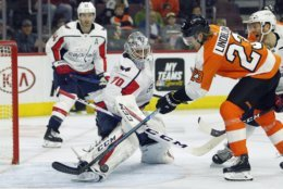 Washington Capitals' Braden Holtby kicks away a shot by Philadelphia Flyers' Oskar Lindblom during the second period of an NHL hockey game Thursday, March 14, 2019, in Philadelphia. (AP Photo/Tom Mihalek)