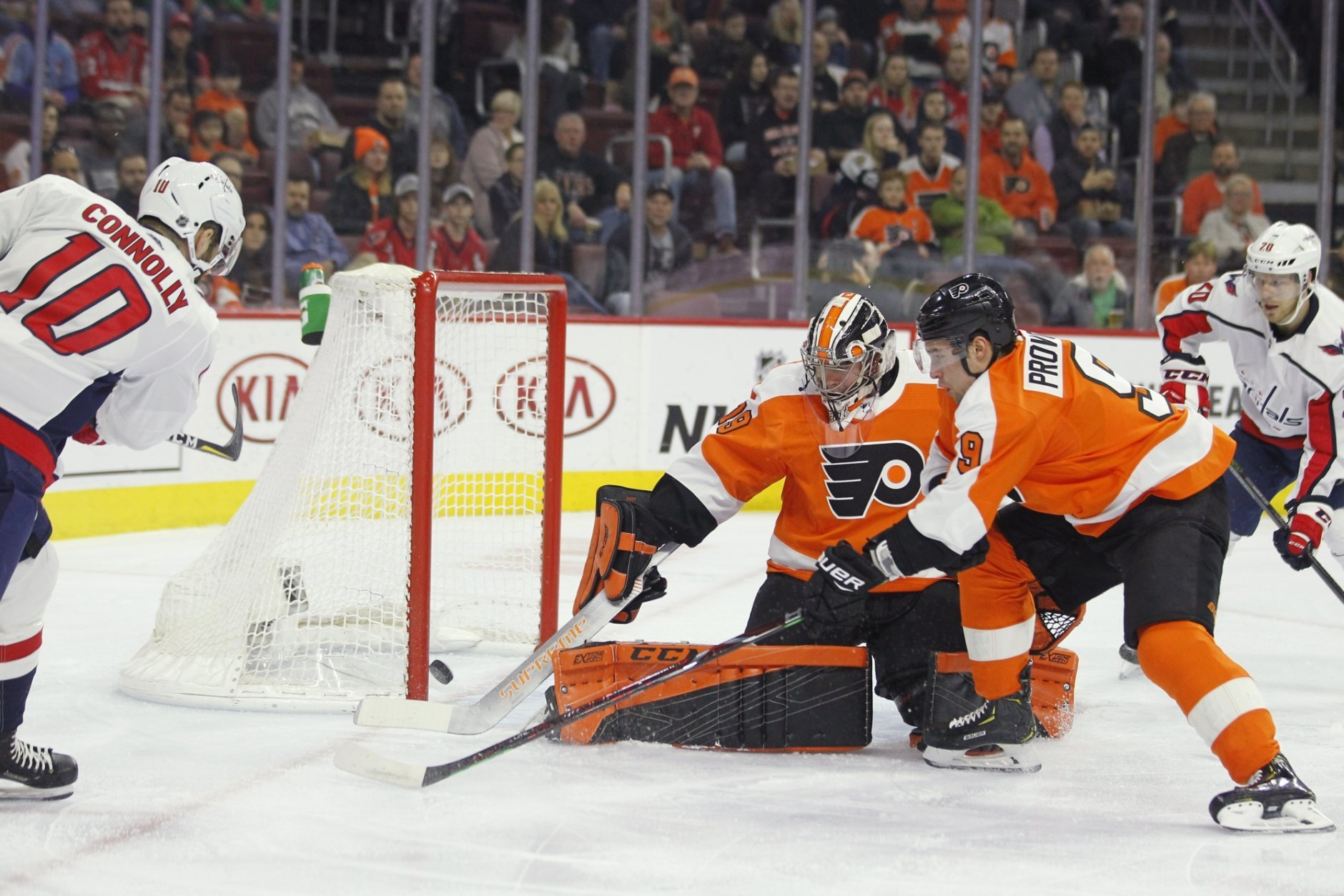 Washington Capitals' Brett Connolly, left, scores past Philadelphia Flyers goalie Carter Hart, center, and Ivan Provorov, right, during the first period of an NHL hockey game Thursday, March 14, 2019, in Philadelphia. (AP Photo/Tom Mihalek)