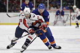 Washington Capitals' Nic Dowd (26) fights for control of the puck with New York Islanders' Devon Toews (25) during the second period of an NHL hockey game Friday, March 1, 2019, in Uniondale, N.Y. (AP Photo/Frank Franklin II)