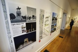 A visitor to the Valentine museum looks over one of the proposals for changes to Confederate statues on Monument Avenue in Richmond, Va., Tuesday, Feb. 26, 2019. A new exhibit in Richmond showcases designs and ideas on what to do with Richmond's Confederate monuments. Local artists hope the exhibit will spark conversations about how to accurately document the city's history while not glorifying Confederate leaders. (AP Photo/Steve Helber)