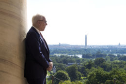 Philanthropist David Rubenstein stands by a portico pillar of the historical Arlington House at Arlington National Cemetery in Arlington, Va., Thursday, July 17, 2014. The historic house and plantation originally built as a monument to George Washington overlooking the nation's capital that later was home to Confederate Gen. Robert E. Lee and 63 slaves will be restored to its historical appearance after a $12.3 million gift from Rubenstein. (AP Photo/Cliff Owen))