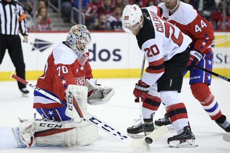 06c8576c42e Washington Capitals goaltender Braden Holtby (70) and New Jersey Devils  center Blake Coleman (20) reach for the puck during the first period of an.