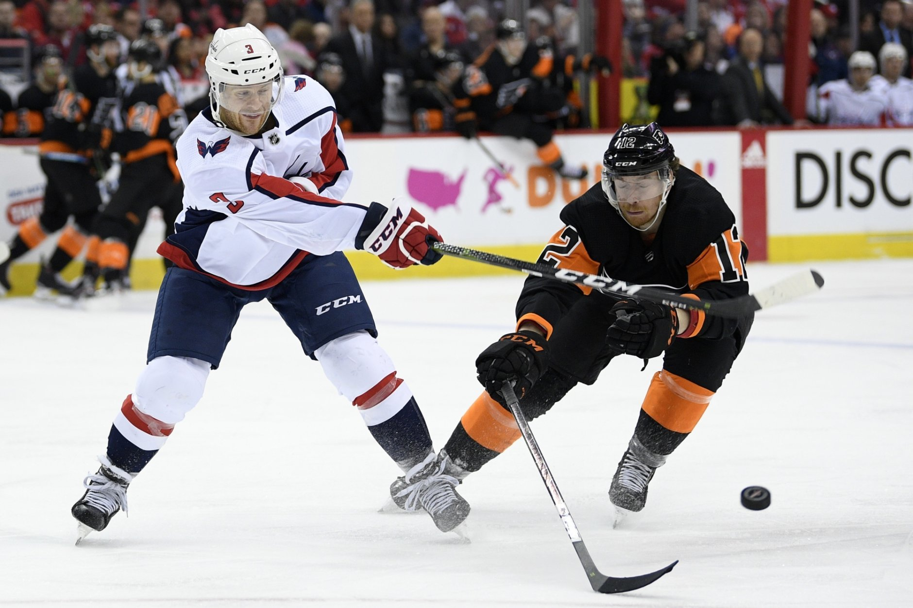 Washington Capitals defenseman Nick Jensen (3) battles for the puck against Philadelphia Flyers left wing Michael Raffl (12) during the second period of an NHL hockey game, Sunday, March 24, 2019, in Washington. (AP Photo/Nick Wass)