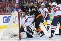 Philadelphia Flyers right wing Jakub Voracek (93), of the Czech Republic, collides with Washington Capitals goaltender Braden Holtby (70) during the second period of an NHL hockey game, Sunday, March 24, 2019, in Washington. Capitals left wing Carl Hagelin (62) and defenseman Brooks Orpik (44) look on. (AP Photo/Nick Wass)