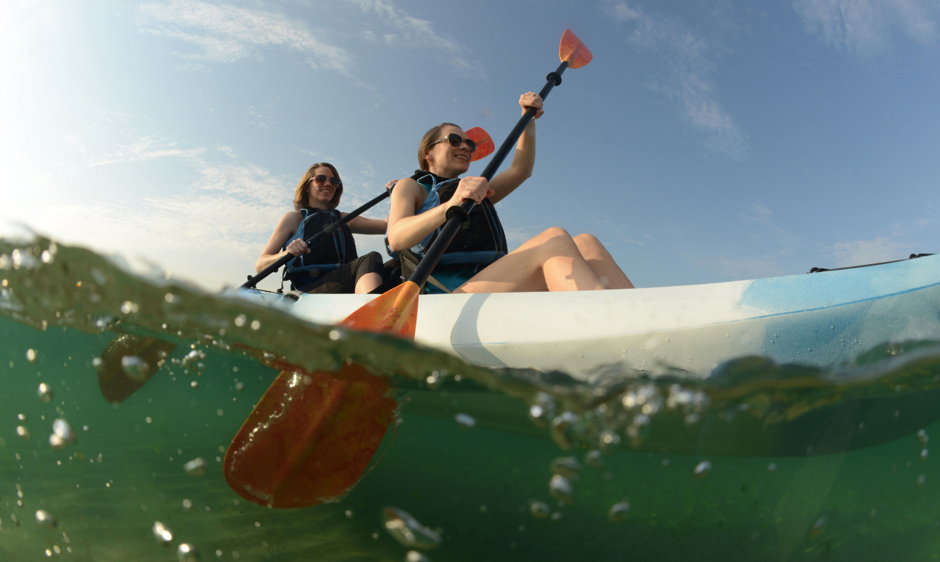 Two young women paddling blue kayak in Atlantic Ocean off of the coast of Florida