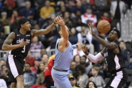 Washington Wizards guard Bradley Beal (3) and forward Bobby Portis (5) battles for the ball against Memphis Grizzlies center Jonas Valanciunas, center, during the first half of an NBA basketball game, Saturday, March 16, 2019, in Washington. (AP Photo/Nick Wass)