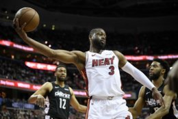 Miami Heat guard Dwyane Wade (3) holds the ball against Washington Wizards guard Chasson Randle, right, and forward Jabari Parker (12) during the first half of an NBA basketball game, Saturday, March 23, 2019, in Washington. (AP Photo/Nick Wass)