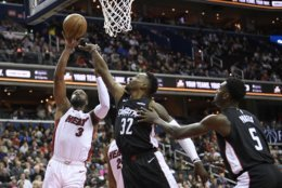 Miami Heat guard Dwyane Wade (3) goes to the basket against Washington Wizards forward Jeff Green (32) and forward Bobby Portis (5) during the first half of an NBA basketball game, Saturday, March 23, 2019, in Washington. (AP Photo/Nick Wass)