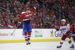 Washington Capitals left wing Andre Burakovsky, left, leaps up for the puck against Carolina Hurricanes defenseman Trevor van Riemsdyk (57) during the first period of an NHL hockey game, Tuesday, March 26, 2019, in Washington. (AP Photo/Nick Wass)