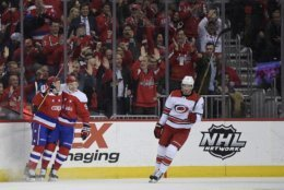 Washington Capitals right wing T.J. Oshie, left, celebrates his goal with center Evgeny Kuznetsov, center, during the first period of an NHL hockey game as Carolina Hurricanes defenseman Brett Pesce (22) skates by, Tuesday, March 26, 2019, in Washington. (AP Photo/Nick Wass)