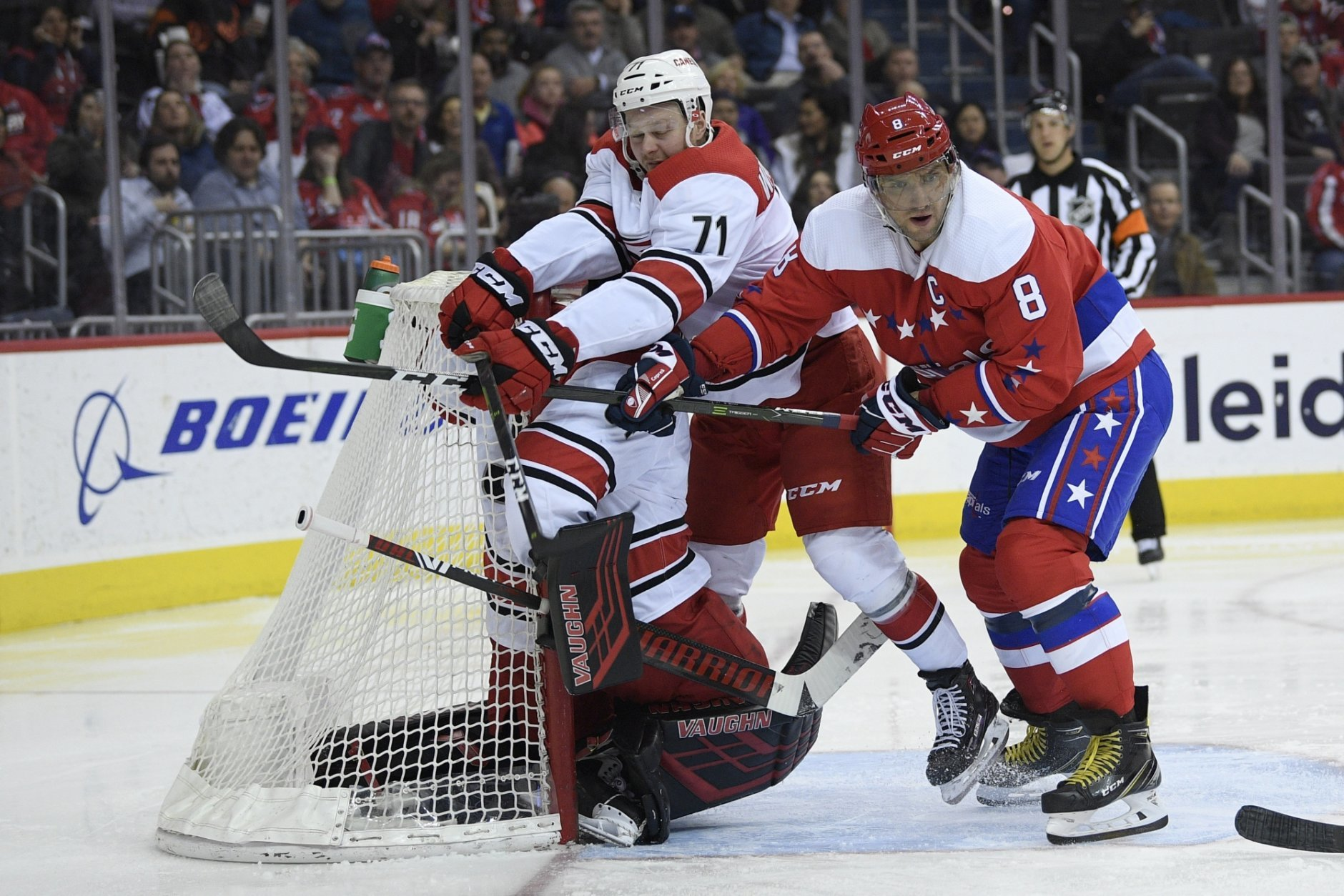 Washington Capitals left wing Alex Ovechkin (8), of Russia, battles with Carolina Hurricanes center Lucas Wallmark (71) and goaltender Petr Mrazek, left, during the second period of an NHL hockey game, Tuesday, March 26, 2019, in Washington. (AP Photo/Nick Wass)