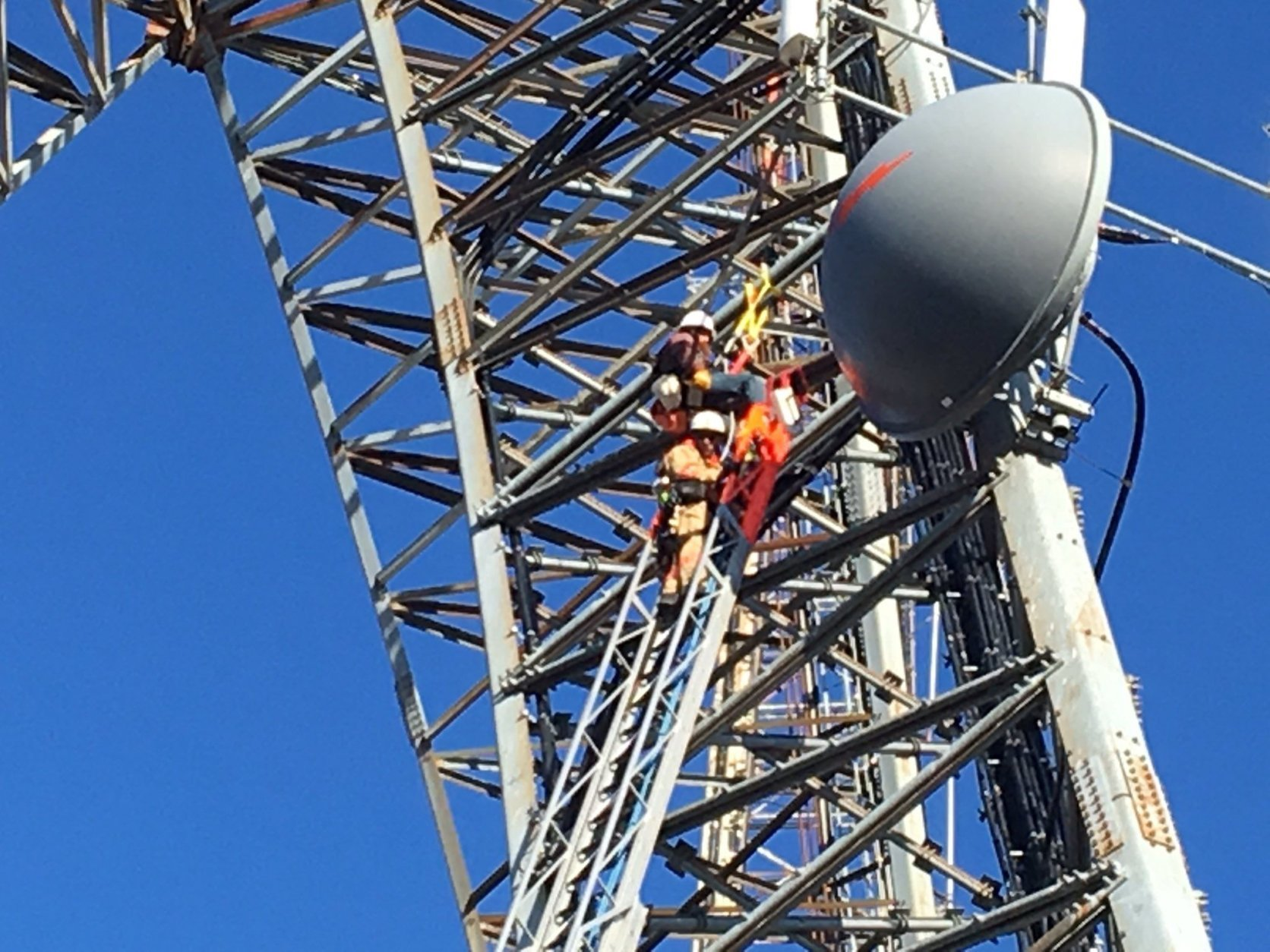 Zoom-in picture of a worker attempting to climb down from a radio tower in D.C. (Courtesy DC Fire and EMS/Twitter)